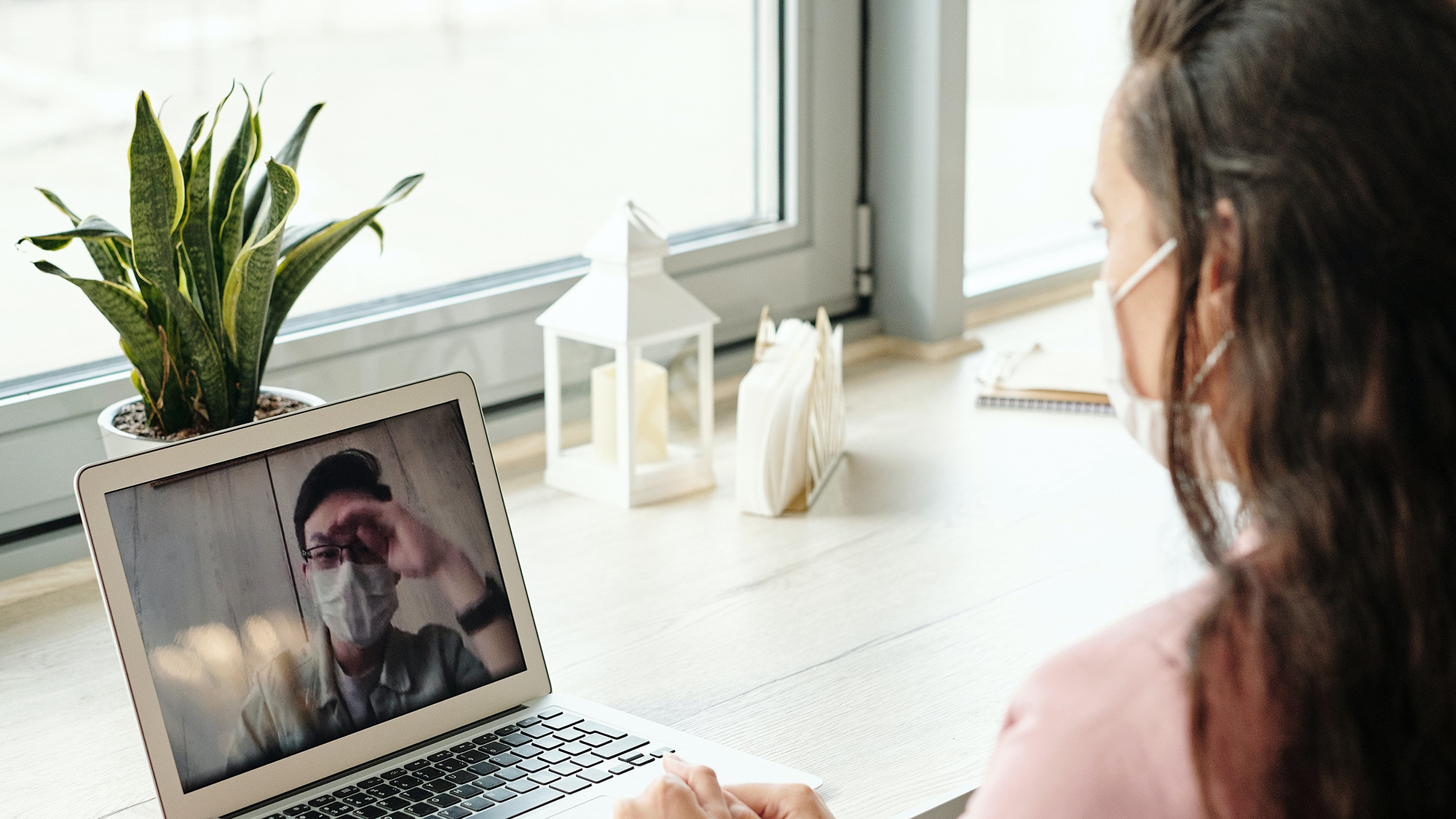 Woman on her laptop, wearing a mask, and video chatting with a man also wearing a mask